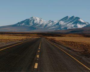 Autoweg in de Atacama woestijn met uitzicht op het Andesgebergte.
