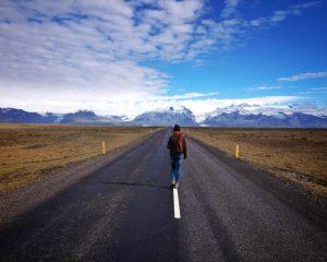 Emma op een autoweg in IJsland met een geweldig uitzicht op een aantal bergen.