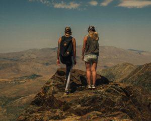 Twee vrouwen op reis in één van de zonnige landen. Ze staan op een berg met uitzicht over het landschap.