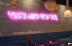 Vegan Junk Food Bar in roze neon verlichting.
